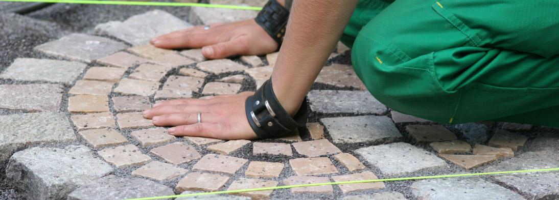 Azubi nach Vollendung einer Pflasterarbeit aus Natursteinen