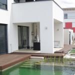 Geometrisch angelegte Wasserflächen um ein modernes Haus - während der Befüllung