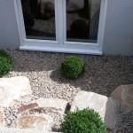 Kleiner Fenster-Vorhof mit Findlingen und Buchs