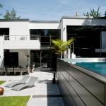 Hochgelegter Pool zu einem Haus im Bauhaus-Stil - eine reizvollle Idee, stilistisch perfekt an das Haus angepasst.