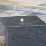 Beleuchtete kleine Wasserfontäne eines Granit-Würfels