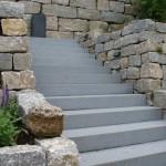 Graue Granit-Trittstufen umsäumt von Muschelkalk-Trockenmauern