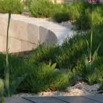 Halbrunde Travertin-Mauer, die eine Holzterrasse begrenzt
