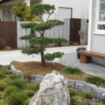 Gestaltung eines Vorgartens mit Findling, Trockenmauern und passenden Stelen
