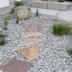 Gestaltung eines Vorgartens mit Trittplatten und minimalistischer Bepflanzung